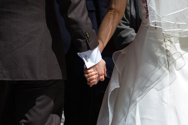 Manželský pár držící se za ruce